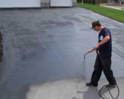 Spraying Driveway Sealant On A Driveway